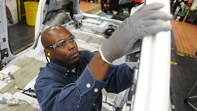 File photo of Nissan employee installing a side-curtain airbag in an Armada SUV as the vehicle passes his station on the assembly line at the company's manufacturing plant in Canton, Miss.