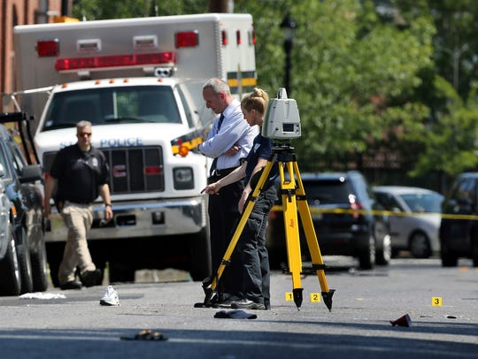 Investigators stand in a street near evidence markers