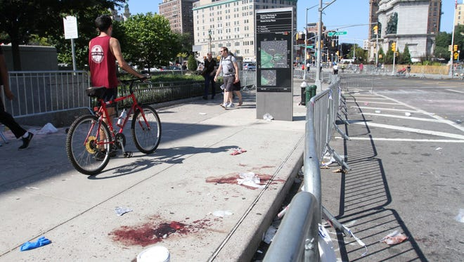 Blood stains remain on a sidewalk Monday where a 24-year-old man was stabbed to death at Grand Army Plaza in Brooklyn before the start of the West Indian Day Parade.
