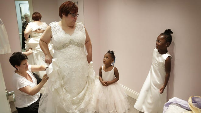 """""""We're excited,"""" April DeBoer said amid her wedding planning, after a battle to overturn a ban on same-sex marriage led to a U.S. Supreme Court ruling. She and daughters Rylee DeBoer-Rowse, 3, and Ryanne DeBoer-Rowse, 5, tried on dresses last month donated by B. Ella Bridal in Plymouth. Seamstress Libby Lescamela ensured a perfect fit."""