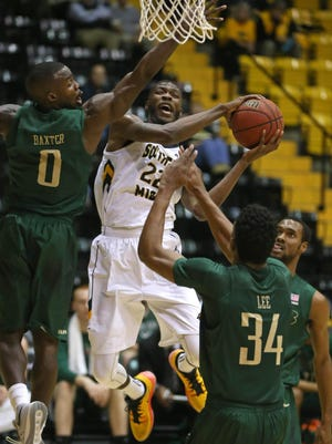 Feb 11, 2016; Hattiesburg, MS, USA; Southern Miss Golden Eagles guard Quinton Campbell (22) attempts a shot while defended by UAB Blazers guard Hakeem Baxter (0) and forward William Lee (34) at Reed Green Coliseum. Mandatory Credit: Chuck Cook-USA TODAY Sports