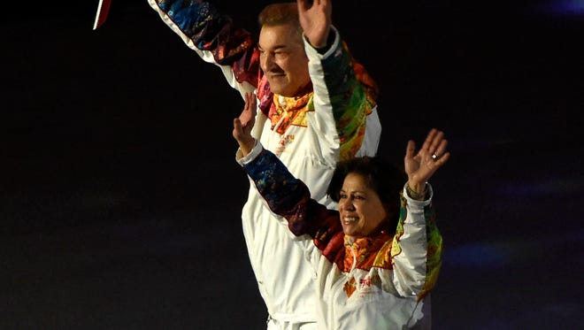 Olympic torch bearers Vladislav Tretyak (left) and Irina Rodnina jointly lit the flame Friday night. A controversy later erupted over a racist tweet by Rodnina directed at President Obama.