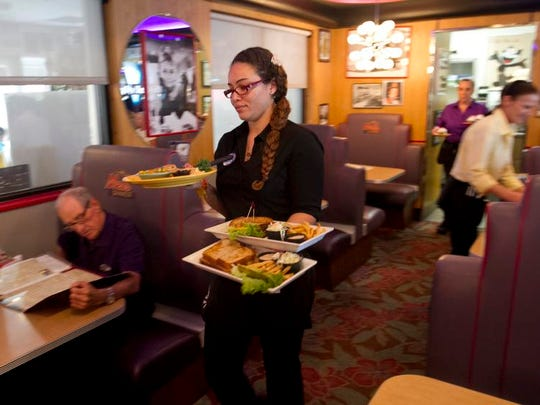 Aja Jones brings food to a table at Mel's Diner in Fort Myers.
