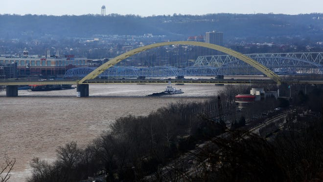 A barge passes under the Daniel Carter Beard Bridge, as seen from the Eden Park overlook on Tuesday morning. Moderate flooding is expected along the Ohio River at Cincinnati this week as roads continue to close due to high water.