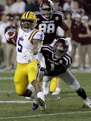 LSU running back Derrius Guice (5) breaks away from Texas A&M defensive back Nick Harvey (1) as he runs for a touchdown during the first quarter of a college football game Thursday, Nov. 24, 2016, in College Station, Texas. (AP Photo/David J. Phillip)