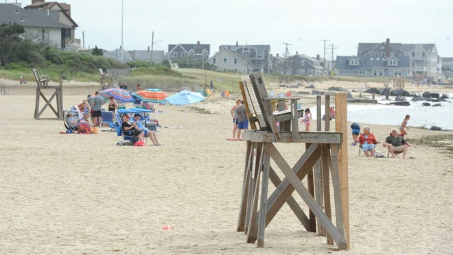 Lifeguard chairs sit empty at Falmouth Heights Beach on Wednesday. Some beaches in town have been short-staffed since at least 10 lifeguards tested positive for the coronavirus and some other employees have quit or refused to work. The town is allowing employees who are awaiting test results to continue working if they are without symptoms.