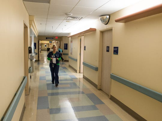 A hospital staff member walks down the hall of the