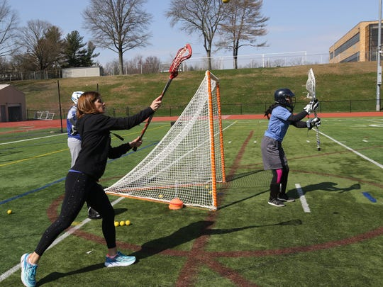 Champ runs drills with lacrosse players at Northern Northern Valley Regional High School at Demarest. In addition to coaching the girls' lacrosse teams there, she also coaches the Dwight-Englewood School'scross-country team.
