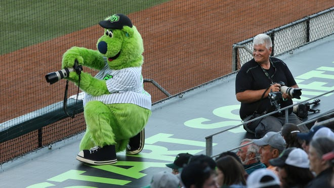 Eugene Emeralds mascot Sluggo, left, borrows a camera from team photographer Gary Breedlove, right, during a game against the Tri-City Dust Devils at PK Park in Eugene. [Chris Pietsch/The Register-Guard, file] - registerguard.com