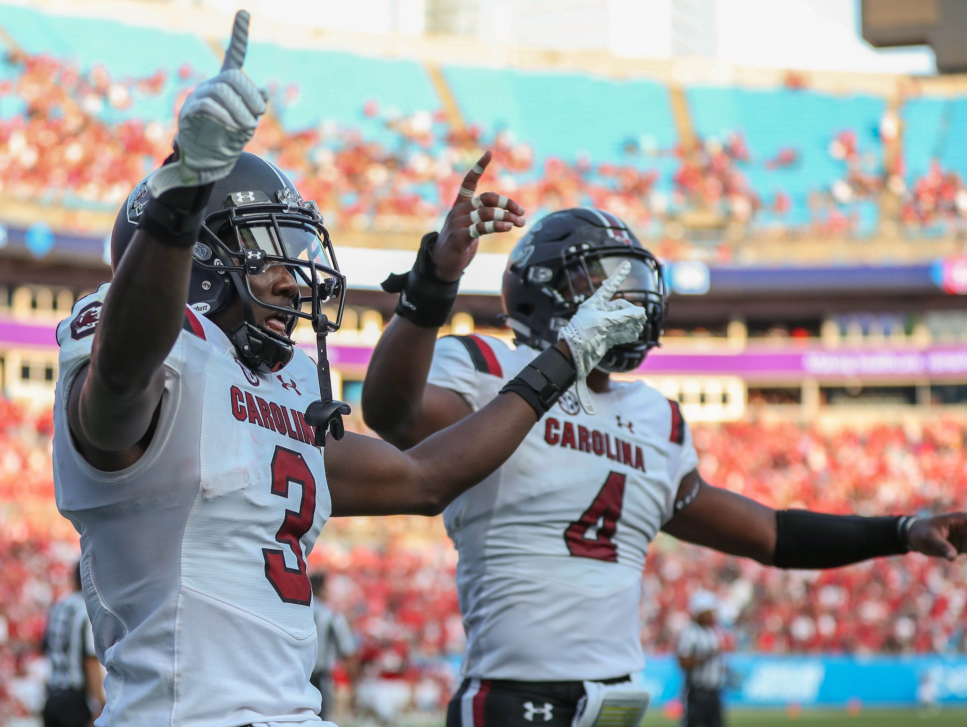 South Carolina Gamecocks defensive back Chris Lammons (3) and linebacker Bryson Allen-Williams (4) celebrate the win over the North Carolina State Wolfpack during the second half at Bank of America Stadium.