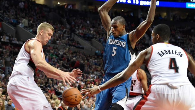 Portland Trail Blazers center Mason Plumlee knocks the ball away from Minnesota Timberwolves center Gorgui Dieng (5) as Trail Blazers forward Maurice Harkless (4) closes in during the first quarter of an NBA basketball game in Portland, Ore., Saturday, April 9, 2016.