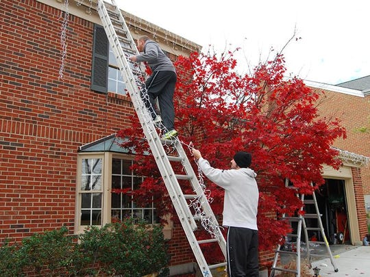 When using a ladder to hang lights, make sure someone is on the ground to keep the ladder steady.