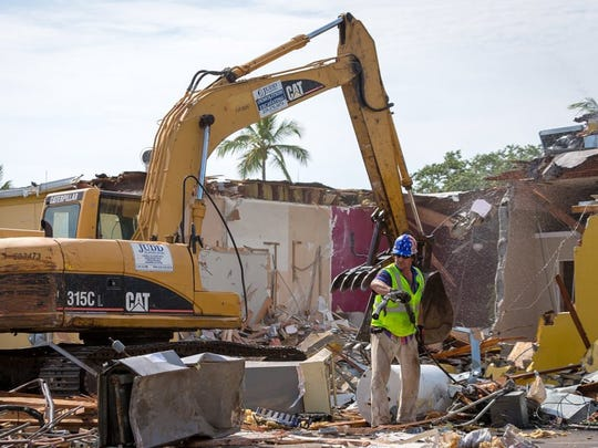 In this file photo, a demolition crew tears down a building near the corner of Fifth Avenue South and Fifth Street South on Wednesday, May 11, 2016, in Naples. Demolition work began Wednesday morning in preparation for demolition of the building to be replaced by a planned 3-story commercial and residential structure by local businessman Phil McCabe. (David Albers/Staff)