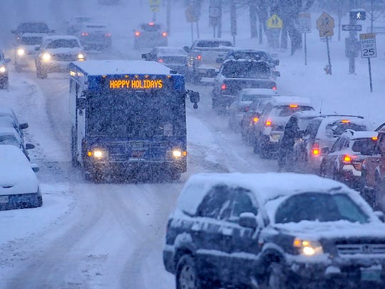 Traffic crawls up Main Street in Burlington as falling snow makes for a tricky evening commute on Friday, December 22, 2017.