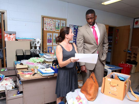 Farid Johnson, the new principal of Stony Point Elementary School, visits kindergarten teacher Lisa Moss' room while she sets it up for the school year Aug. 22, 2017 in Stony Point.