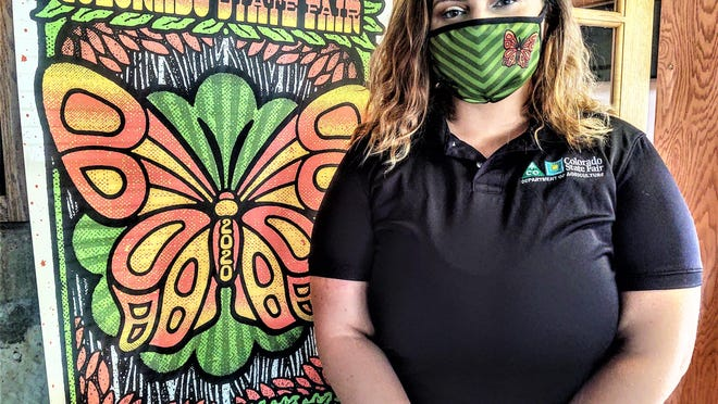 "Tiffany Underwood, marketing coordinator for the Colorado State Fair, wearing the official fair facemask she designed. The ""Walk on the Wild Side"" poster was designed by another Puebloan, Mathias Valdez of Last Leaf Printing."