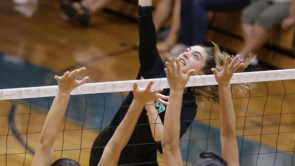 Montwood's Nadia Kern hits into Burges blockers Deandra Allen, left, and Kathrine Moya during their match Tuesday at Montwood High School.
