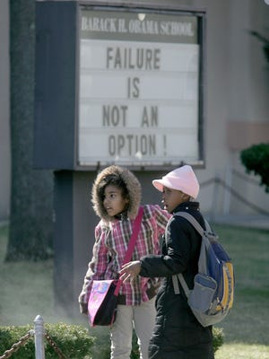 """ASBURY PARK — Students stand outside the Barack Obama Elementary School on Bangs Avenue in 2011, on front of a sign that reads """"Failure is not an option!"""""""