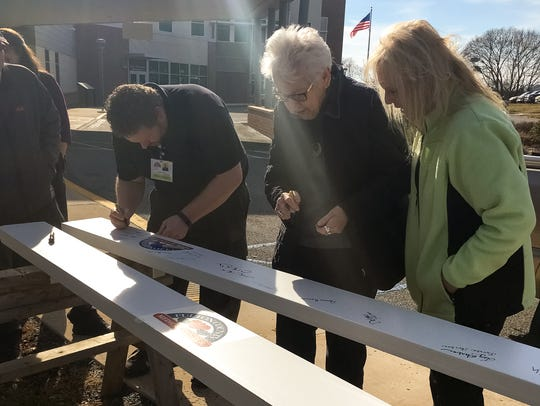 Community members sign their names on a beam outside