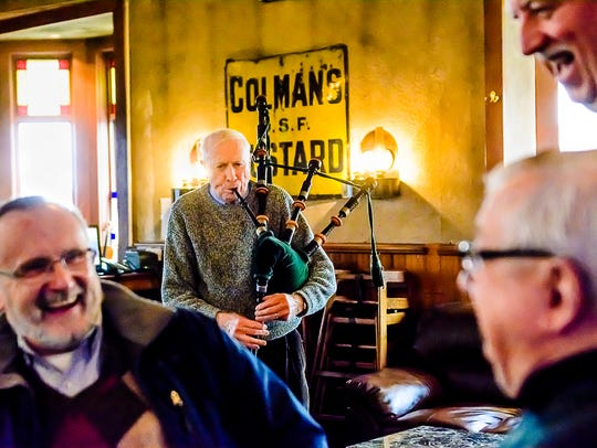 Terry Carroll, center, plays the bagpipes during a