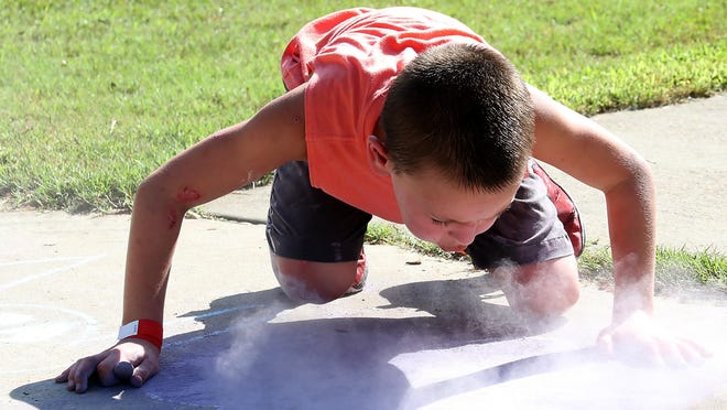 Elijah OKelley blows the chalk away from his drawings on his sidewalk canvas, Saturday, July 11, 2020, during the kid's chalk artist contest in the Barling City Park. Sponsored by the city after having to cancel the Fourth of July event due to COVID-19 concerns, the replacement summer event included frozen treats and drinks and awarded prizes for the best artist in three age groups. Elijah is the 8-year-old son of Alicia and Zachary OKelley.