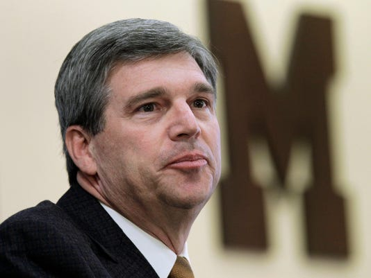 FILE - This is a Jan. 5, 2011, file photo showing University of Michigan athletic director Dave Brandon announcing that head football coach Rich Rodriguez has been fired during a news conference in Ann Arbor, Mich. Brandon has resigned, setting the stage for new leadership at the top of one of the nation's most prominent athletic departments. (AP Photo/Paul Sancya, File)