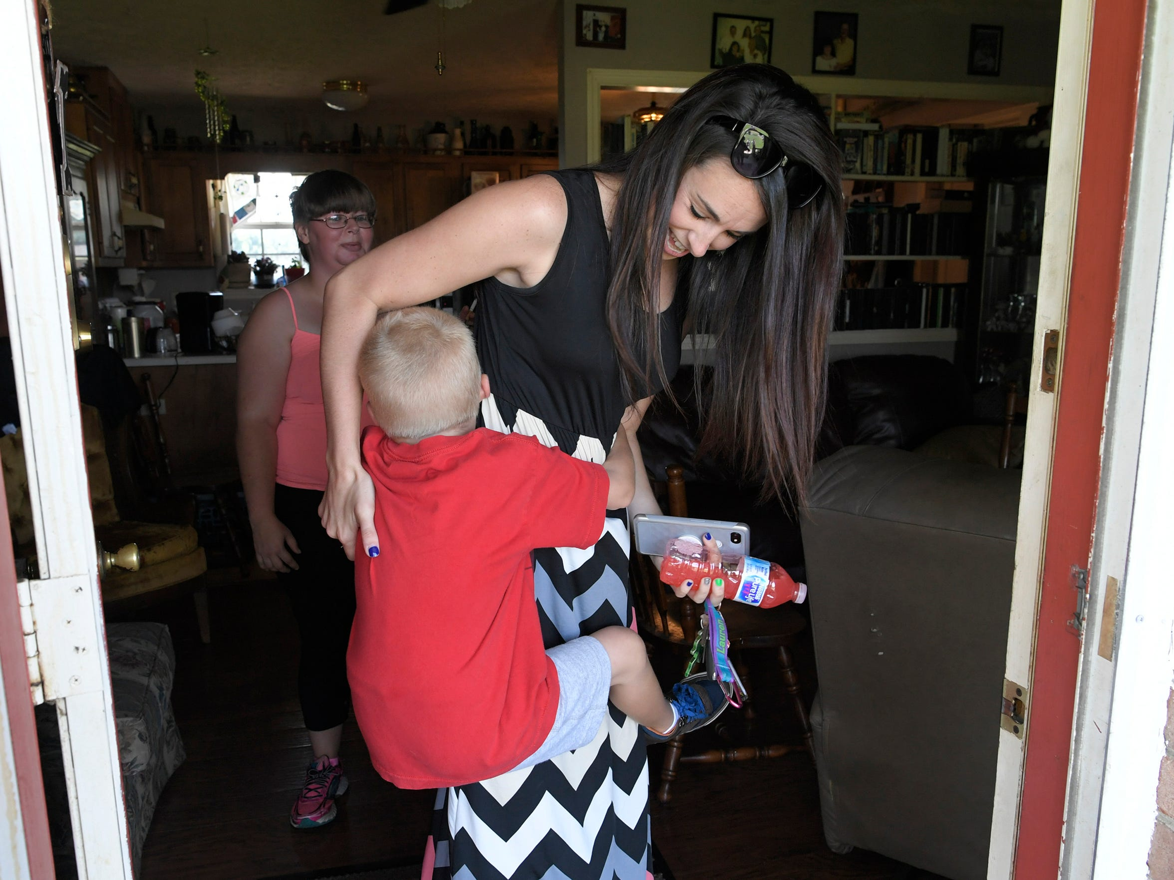 Lacey Lewis, a family intervention specialist with Youth Villages, says goodbye to Bryson Hines, 5, as he tries to stop her from leaving his home on Thursday, July 19, 2018.  Tasha Burragne and her children are part of a pilot program with Youth Villages is doing with DCS to help prevent children from coming into foster care.
