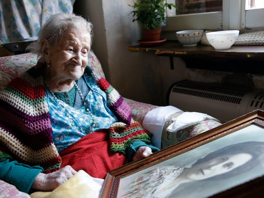 In this June 26, 2015 photo, Emma Morano, 115, looks at an old portrait of herself in her apartment in Verbania, Italy. Morano and Susannah Mushatt Jones, also 115, of Brooklyn, N.Y., are believed to be the last two people in the world with birthdates in the 1800s.