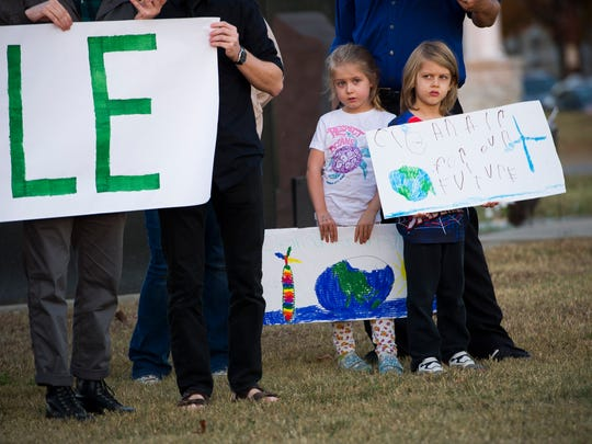 Adelyn Lewis, 6, left, and Harper Lewis, 5, both of Evansville, hold signs with other demonstrators near the Four Freedoms Monument in Evansville, Wednesday, Nov. 16, 2016. Demonstrators marched from the Four Freedoms Monument to Vectren headquarters to protest Vectren's continued use of coal-fired power plants.
