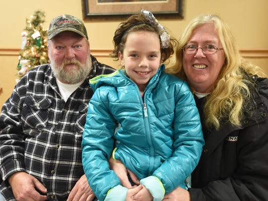 Lakota Anderson, who turns 9 years old today, poses with her longtime friends, Roger and Kim Benter, who are caring for the little girl after she lost her mother to a heart attack on Dec. 13.