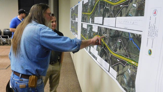 Hendersonville resident Gene Logan points to a map showing a proposed widening of Interstate 26 while talking to an unidentified engineer.