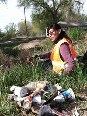"""A frame from """"Mayors of Shiprock"""" shows a member of the Northern Diné Youth Committee participating in the group's Earth Day community clean up."""