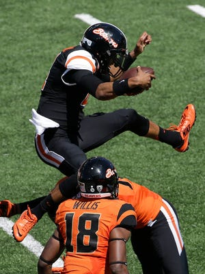 Oregon State quarterback Seth Collins leaps over defender Kendall Hill during the second half of their NCAA college football spring game in Corvallis, Ore., Saturday, April 18, 2015.