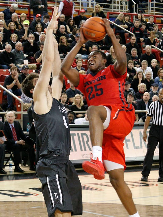 Davidson's Andrew McAuliffe, left, defends as Dayton's Kendall Pollard, right, goes to the basket during the second half of an NCAA college basketball game in Davidson, N.C., Tuesday, Jan. 20, 2015. Davidson won 77-60. (AP Photo/Bob Leverone)