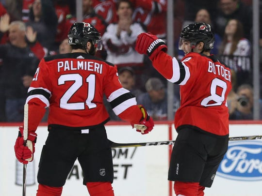 New Jersey Devils right wing Kyle Palmieri (21) and New Jersey Devils defenseman Will Butcher (8) celebrate Butcher's goal during the first period of their game against the New York Rangers at Prudential Center.