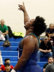 An exhausted Loma Thomas of McKean (seeded 4th) celebrates after beating A.I. du Pont's Juan Jones (5th) at heavyweight in the quarterfinal round of the individual state DIAA tournament at Dover High School Friday.