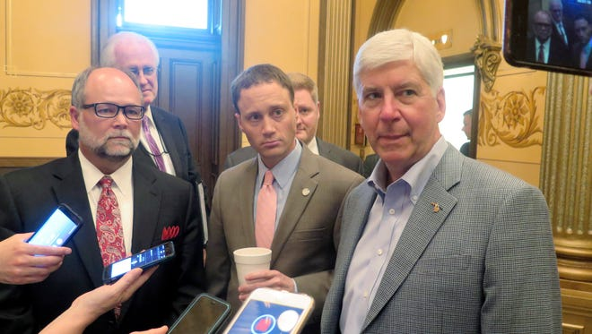 In this June 13, 2017 file photo, Michigan Gov. Rick Snyder, right, House Speaker Tom Leonard, center, and Senate Majority Leader Arlan Meekhof, left, speak to reporters at the Capitol in Lansing, Mich. New economic development tax incentives and the cost of retirement benefits for public-sector workers dominated Michigan's legislative agenda in 2017. The Republican governor signed 245 bills as of Thursday, Dec. 21, with many more awaiting his signature after a burst of voting in recent weeks.