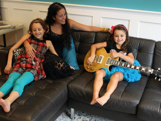 Middletown resident Andrea Verdone Gorsegner and her daughters Natalie (right) and Hannah (left) play with an Jon Bon Jovi autographed guitar that will be auctioned off. Andrea has raised more than $250,000 for research on a variety of childhood cancers and has another big fundraising event next weekend. Her daughter Natalie is in remission from leukemia, the family is photographed at their home on Friday September 11,2015