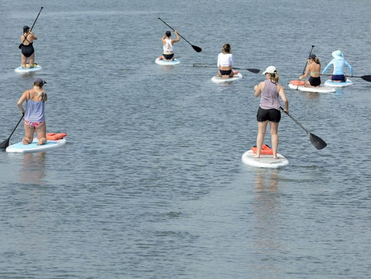 A group of paddle boarders leave Manasquan's Fourth