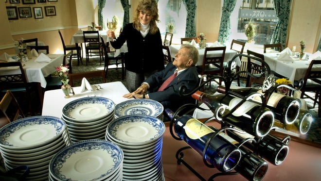 George Watts & Son Inc. and The Watts Tea Shop are closing Dec. 31. The company, established in 1870, will continue to operate as an online entity. In this April 4, 2004, photo, restaurant manager Sue Thome holds up a glass of wine  as owner George Watts, looks on.