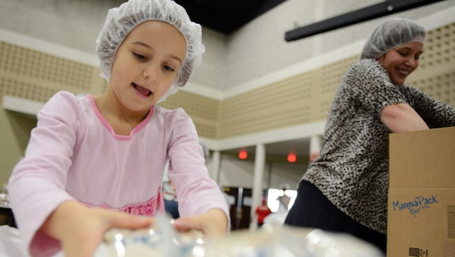 Mattie Larsen, 7, helps her mom, Julie, pack boxes during the Feed My Starving Children MobilePack on Tuesday at Green Bay Community Church in Howard. The family came from Door County to participate.