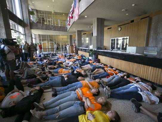 """High school students participate in a """"die-in"""" in the"""