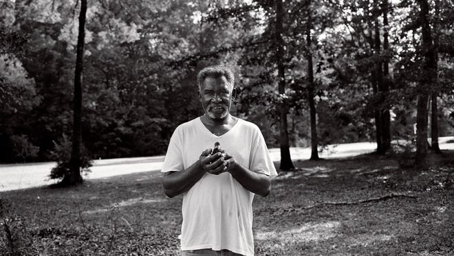 """Levon Brooks loved all kinds of animals. He's shown here holding a baby chick at his home, where he also had turkeys, doves, geese and other birds. From """"Levon and Kennedy"""" © Isabelle Armand."""