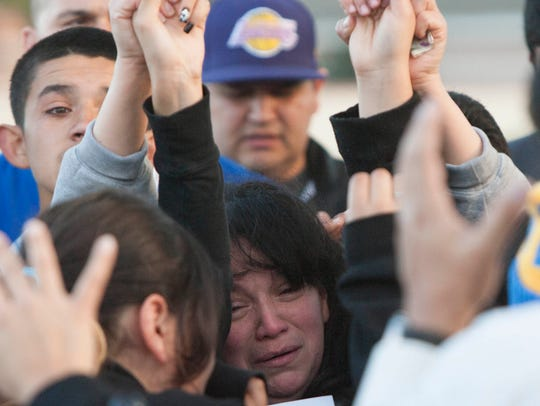 Marisa Lopez cries and prays with family members and