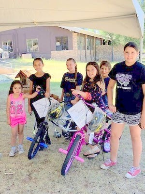 Ruidoso Middle School Braves Cheerleaders enjoy the bikes given by the Masons.