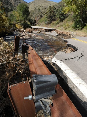 Guard rail along Buckhorn Canyon Road goes down into a washed out road in the Stove Prairie area Tuesday Sept. 24, 2013.