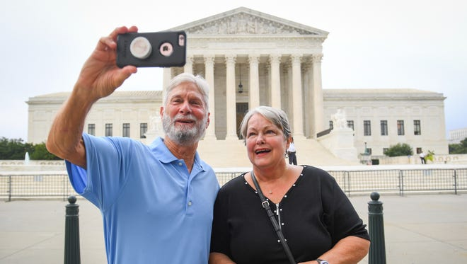 Pat and Kathy Sims, visiting Washington, D.C., from Charlotte, N.C., snap a selfie outside of the United States Supreme Court on the morning of Justice Brett Kavanaugh's first day on the job.