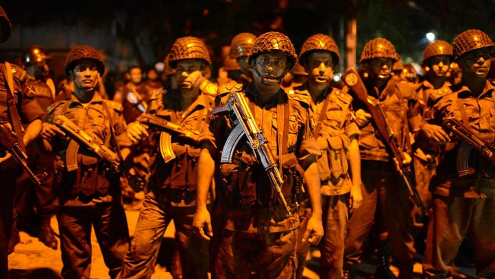 Bangladeshi security officers stand guard near a restaurant
