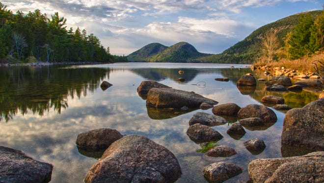 Tall trees and rolling mountains reflect in the still waters of Jordan Pond in Acadia National Park in Maine. Lakes and ponds add shimmering contrast to Acadia's forested and rocky landscape. Within or adjacent to the park, you can explore 14 great ponds and 10 smaller ponds.