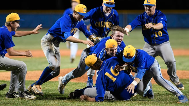 Caldwell County players rush the mound after winning the Second Region championship over Union County 6-2 in Marion Wednesday, May 31, 2017.